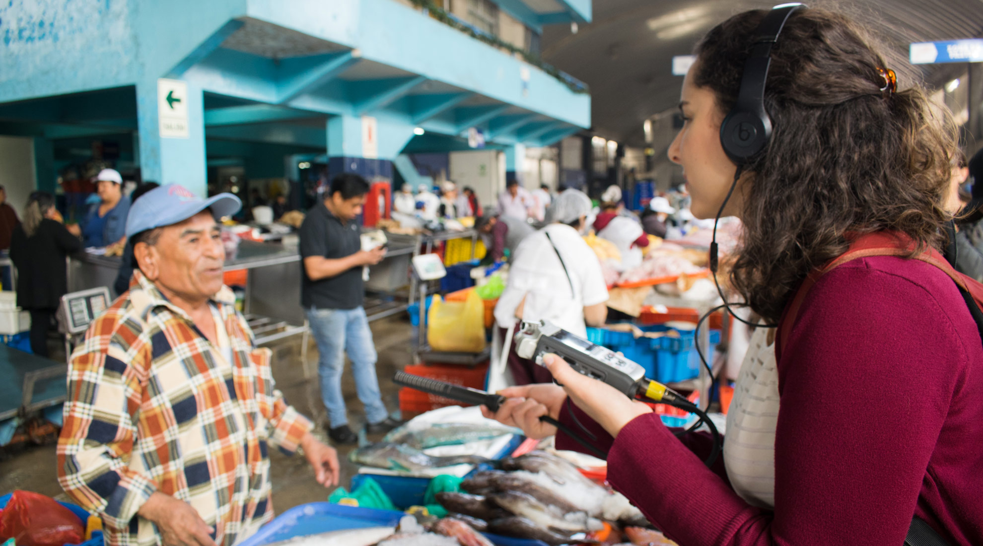 A Global Reporting Program student reporting at a fish market in Peru