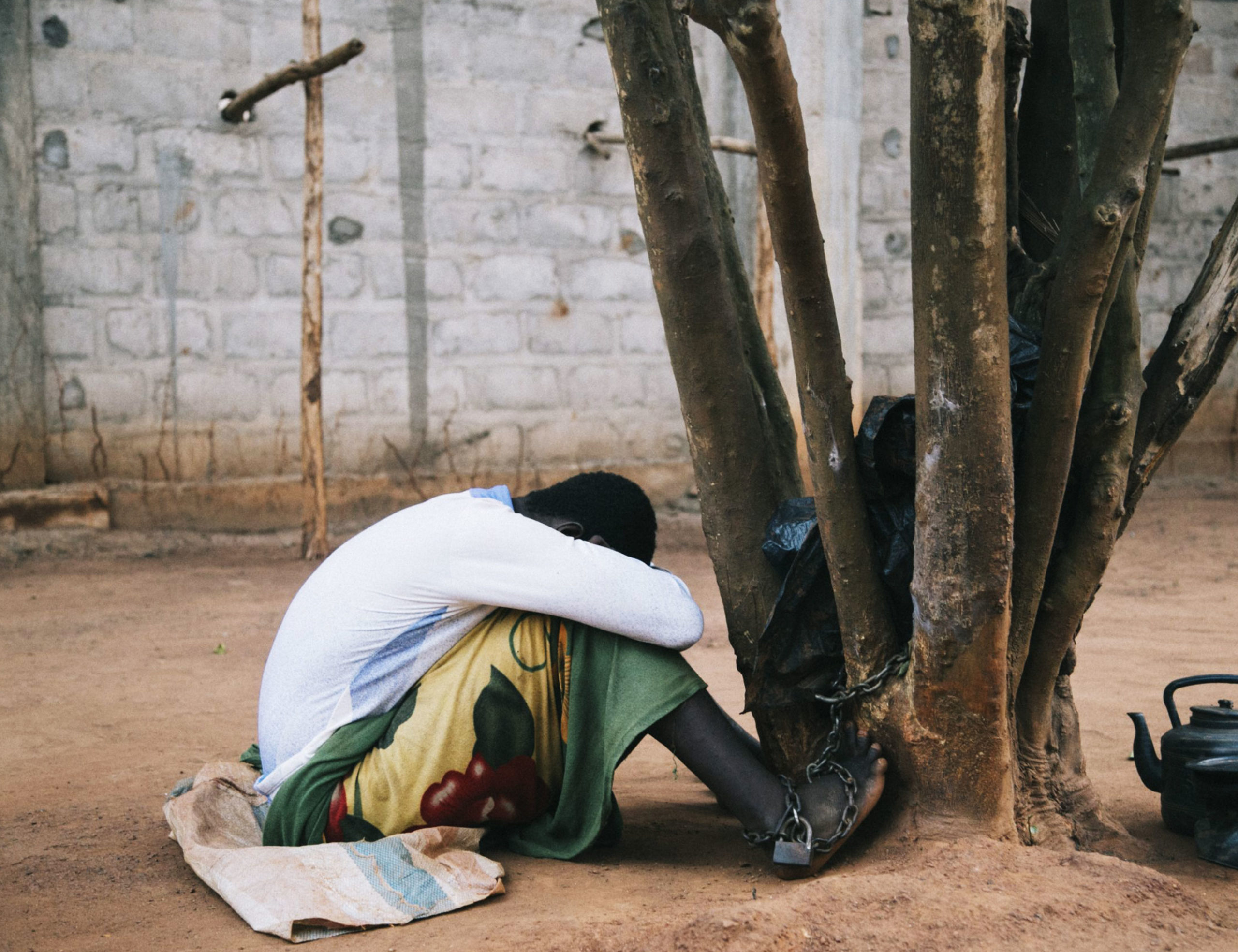 Person chained to tree in a prayer camp